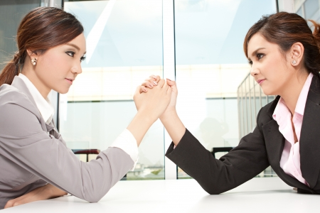 Two young asian co-workers aggressively arm wrestling for dominance