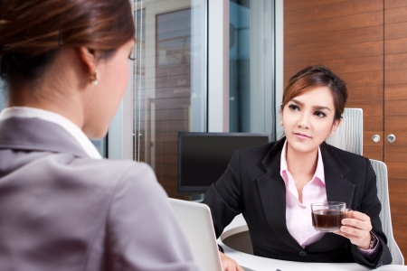Two businesswomen during business conversation in an office Stock Photo
