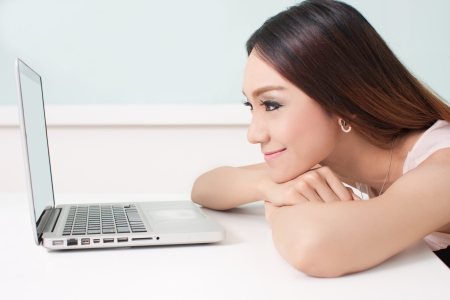 Young beautiful happy woman looking in to laptop