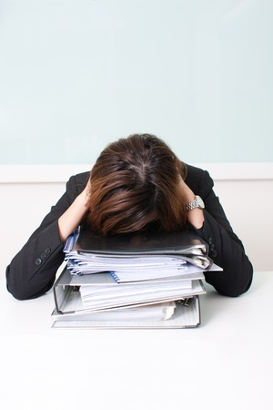 Young businesswoman sitting holding head with hands crouch on pile of folders