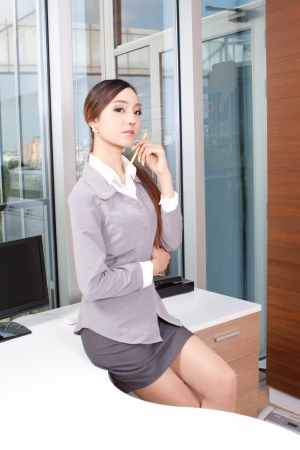 Confident young businesswoman sitting on the desk with pencil in hand