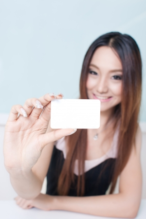 Beautiful young woman  showing and handing a blank business card. photo