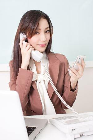 Young business woman multitasking using two phones in office Stock Photo