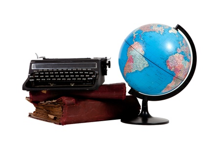 Vintage typewritter on stack of old books with globe on white background Editorial