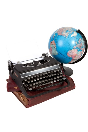Vintage typewritter on stack of old books with globe on white background Éditoriale