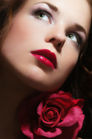 pink lips: Close-up portrait of beautiful woman with green eyes and large red pink rose