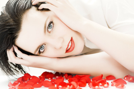 20 24: Young woman laying on floor with rose petals. Stock Photo