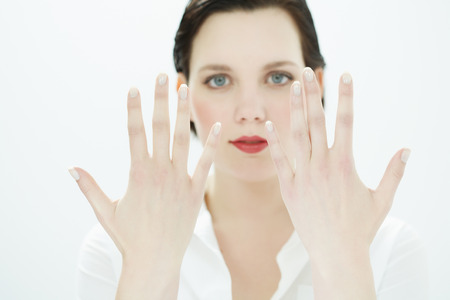20 24: Young woman on neutral background showing both hands.