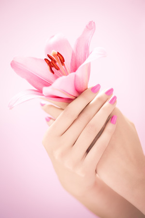 Closeup of female hands with manicure holding a lily flower.