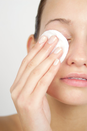 Young woman cleansing her face and applying lotion. Skincare concept. Banco de Imagens