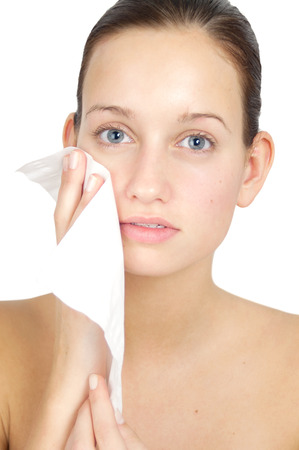 Young woman cleansing her face and applying lotion. Skincare concept. Stok Fotoğraf