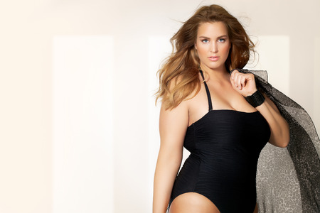 Beautiful plus size model wearing swimsuit and sunglasses.