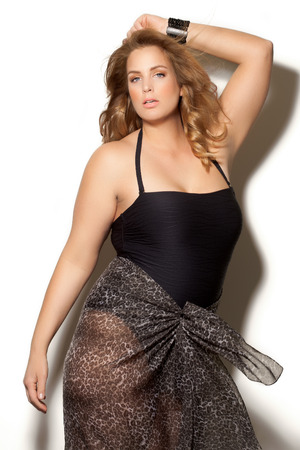 Beautiful plus size model wearing swimsuit and sunglasses.