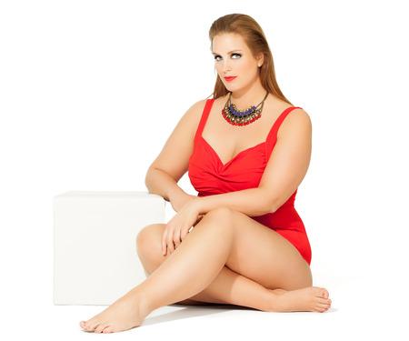 Beautiful plus size model wearing red swimsuit.