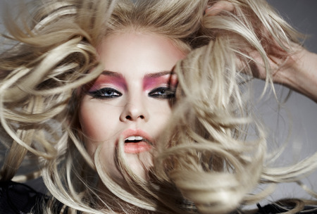 wind blown hair: Closeup of a model spotlit with her hair blown all sides by wind. Stock Photo