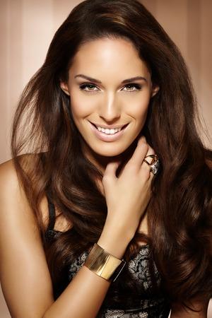 Beautiful woman with long dark hair posing on beige background. Banco de Imagens