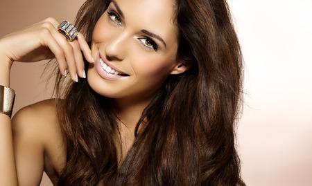 Schöne Frau mit langen dunklen Haaren posiert auf beige Hintergrund.