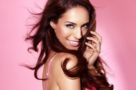 capelli lunghi: Bella donna posa in lingerie su sfondo rosa lucido. Archivio Fotografico