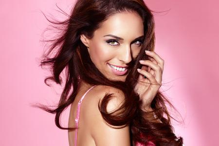 schoonheid: Mooie vrouw poseren in lingerie op roze glanzende achtergrond.