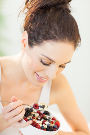 Woman eating fresh made muesli breakfast dish with oats, fresh berries. Smiling healthy eating European girl.