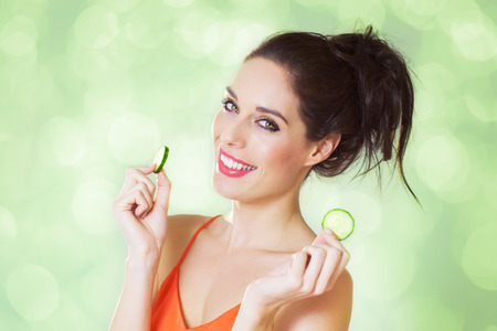 heathy diet: Happy girl with cucumber slices over green sparkling shiny background.