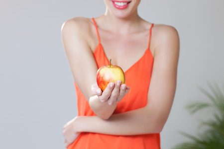 heathy diet: Cropped stock image of a girl giving fresh apple. Indoors over gray background. Healthy detox goals.