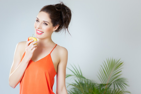 heathy diet: Young girl with red apple. Orange color. Healthy eating concept indoors. Stock Photo