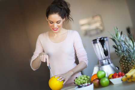 Smiling woman in kitchen cutting melon. Fruit arranged for healthy eating. Food preparation. Blender for making smoothie.