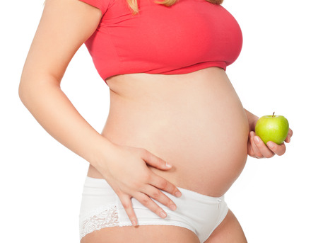 cropped shots: Torso of a pregnant woman with green apple.