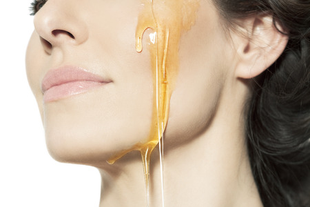 Closeup of a female cheek with honey. Archivio Fotografico