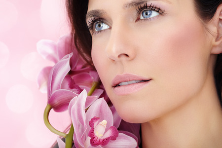 brown hair blue eyes: Closeup of a beautiful woman with pink orchids.