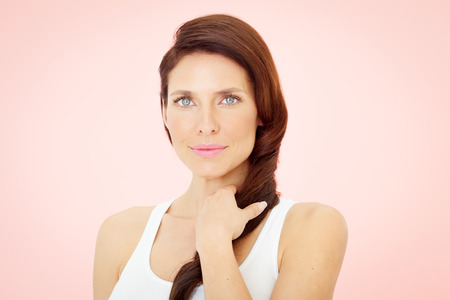 30 years: Beautiful woman with blue eyes on pink background. Stock Photo
