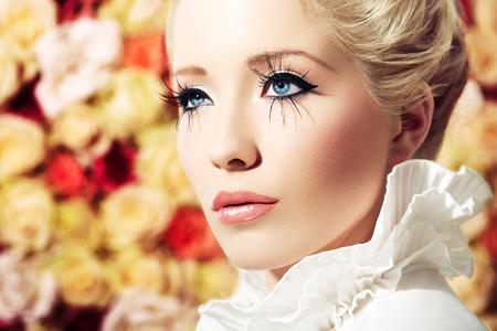 rubia ojos azules: Alto clave belleza visual con rubia modelo de pie en el fondo de rosas.