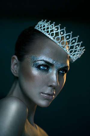 glitter makeup: Model with silver glitter makeup wearing tiara. Available light 800 iso and slight grain. Stock Photo
