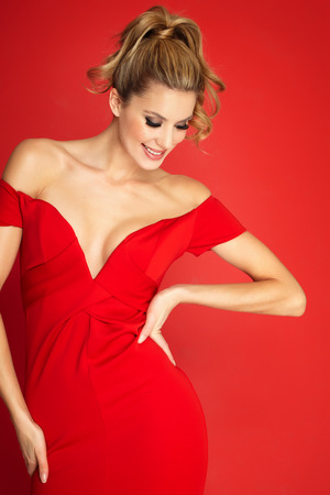 evening dress: Lady in red dress over red background. Stock Photo