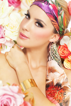 Fashion woman in silk shawl surrounded by colorful flowers. photo