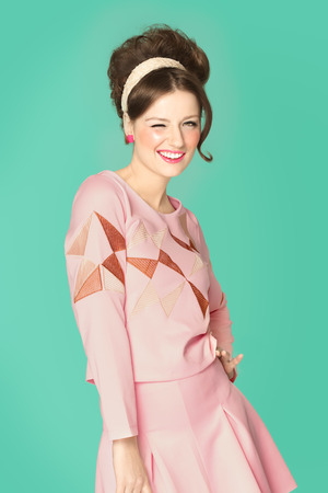 Woman in sixties style fashion posing with wink. Pink and cyan retro colors. Sixties hairstyle.