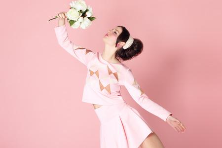 Chica de moda estilo años sesenta con el ramo de flores sobre fondo rosa. Romantic concepto feminidad positiva encantador.