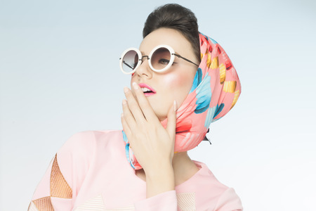 60s: Classy chic sixties style fashion retro woman. Sunglasses and silk scarf. Stock Photo