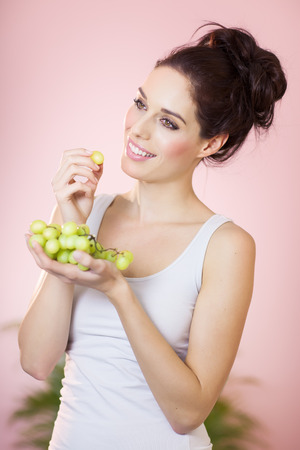 heathy diet: Happy girl with green grapes over pink background indoors.