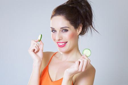 fresh girl: Happy fresh girl with cucumber slices over studio background. Stock Photo