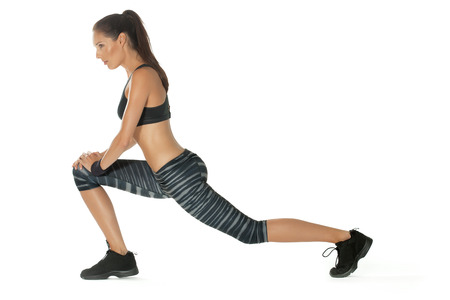 lunges: Young woman posing in fitness outfit.