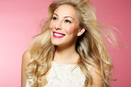 cabello rubio: Mujer hermosa con el pelo largo y rubio y maquillaje bonito que presenta en el fondo de color rosa.