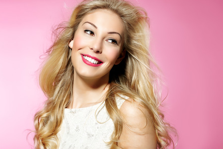 pink posing: Beautiful woman with long blond hair and nice makeup posing on pink background. Stock Photo