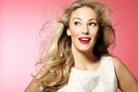 Beautiful woman with long blond hair and nice makeup posing on pink background. Banco de Imagens