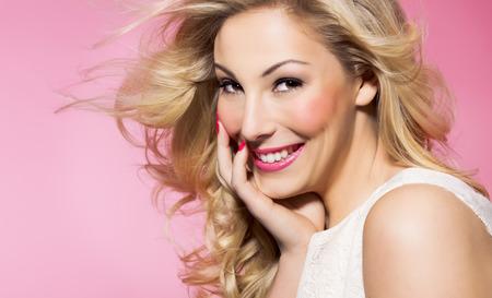 Belle femme avec de longs cheveux blonds et belle maquillage posant sur fond rose. Banque d'images - 37576947