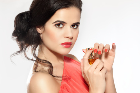 Brunette model posing with a bottle of perfume.