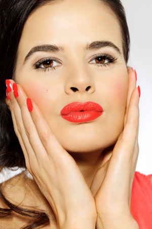 Closeup of a beautiful Latina woman with kissing gesture and bright red makeup.