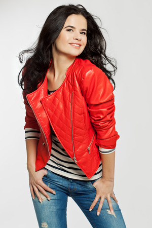 Young woman with long dark hair posing in red leather bomber and blue jeans. Stock Photo
