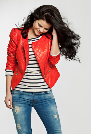 long dark hair: Young woman with long dark hair posing in red leather bomber and blue jeans. Stock Photo
